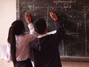 """Pupils writing on the blackboard in a village school in Laos"". Foto de dominio público por Masae en Wikimedia Commons"