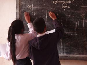 """Pupils writing on the blackboard in a village school in Laos"". Foto de dominio público por Masae en Wikimedia Commons"